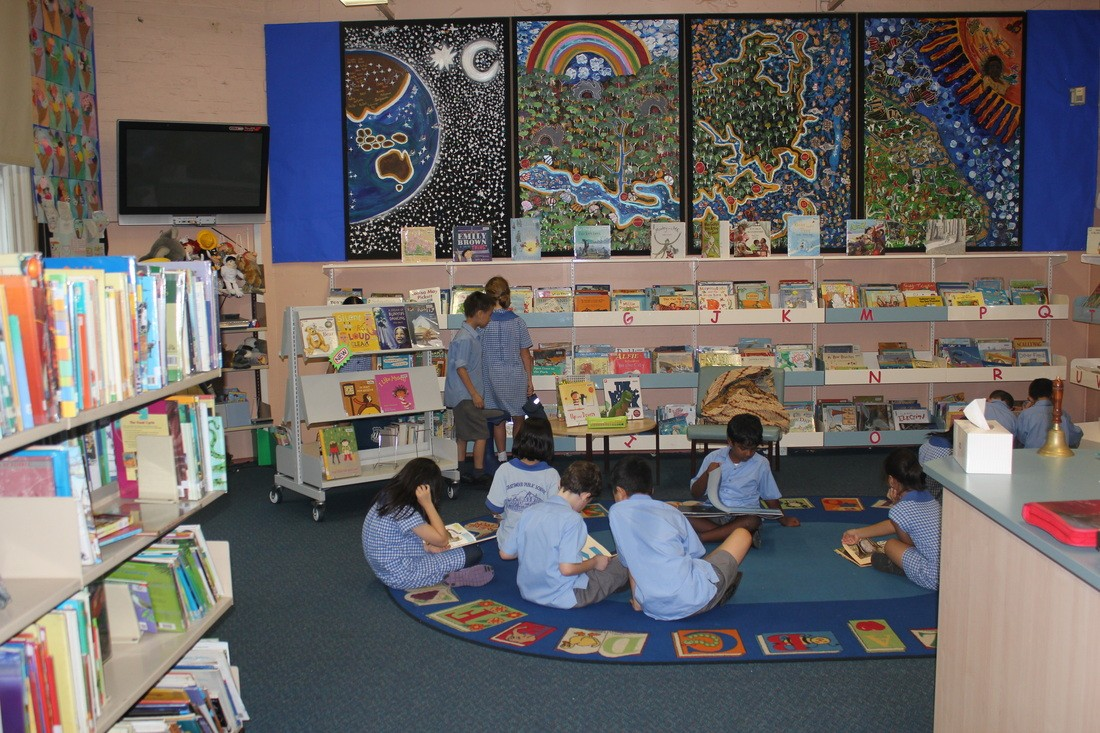 Students reading and selecting books in our library